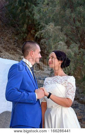 AGIOS NIKOLAOS, CRETE - SEPTEMBER 17, 2016 - Young bride and groom looking at each other in the port area Agios Nikolaos Crete Greece Europe, September 17, 2016.