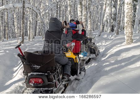 Athletes snowmobile while traveling through the mountains of the Southern Urals. Womens photographed a winter forest to your smartphone.