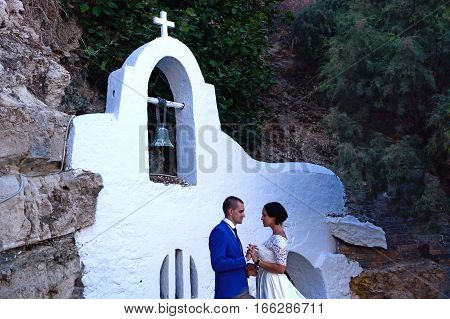 AGIOS NIKOLAOS, CRETE - SEPTEMBER 17, 2016 - Young bride and groom looking at each other in front of a small shrine in the port Agios Nikolaos Crete Greece Europe, September 17, 2016.
