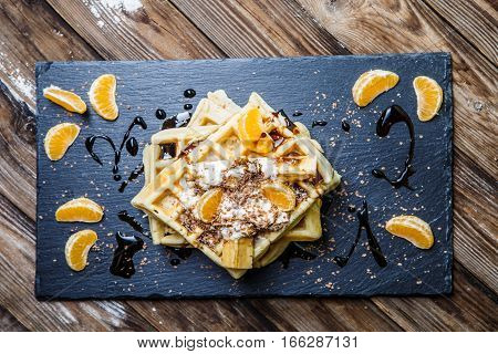 Blackboard with Viennese waffles with topping on wooden table