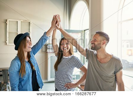 Group of three young people standing and giving gesture 'high five' to each other in light office.