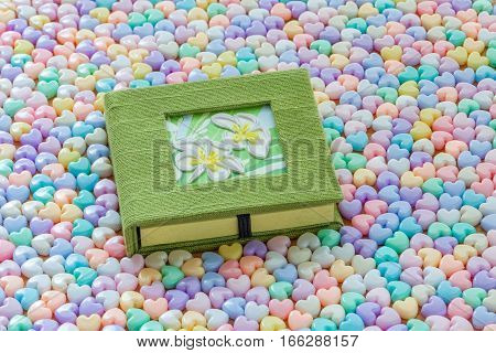 Green notebook and flower on cover placed on center of pile colorful soft pastel heart shaped beads background Valentine theme.