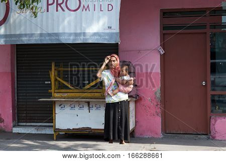BALI, INDONESIA - AUGUST 30,2012: Young woman with a small child walking on the street
