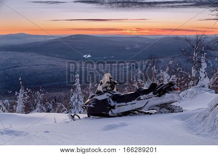 Snowmobile stands on a hillside at sunset.