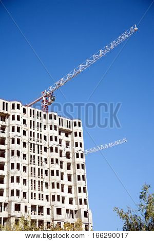 Big hoisting tower cranes and top section of modern construction building over cloudless sky, Vertical photo