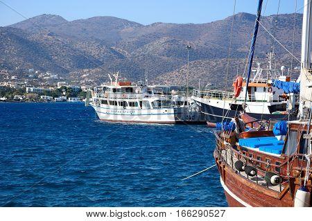 AGIOS NIKOLAOS, CRETE - SEPTEMBER 17, 2016 - Yacht and cruise boats in the harbour with the mountainous coastline to the rear Agios Nikolaos Crete Greece Europe, September 17, 2016.