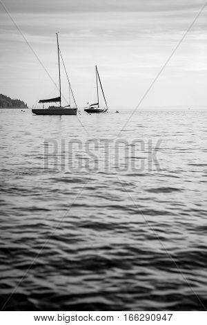A pair of yachts floating gently on the calm waters of Lake Garda Italy.