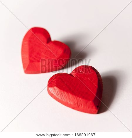 A pair of red wooden carved hearts isolated on white.