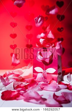 A luxurious gift presented amongst love hearts and falling rose petals set against a red background.