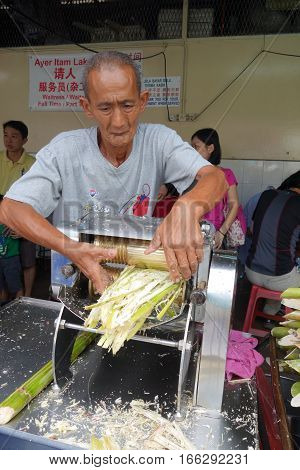 Vendor Prepares Fresh Sugar Can Juice In A Kiosk