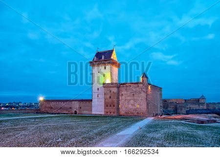 NARVA, ESTONIA - JANUARY 2, 2017: Night view of Hermann Castle Museum on the bank of The Narva (Narova) River. On the right side is fragment of Ivangorod Fortress in Russian Federation