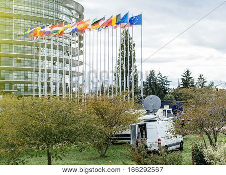 Tv Televison Truck with multiple Satellite parabolic antennas and fiber optic cables going inside reporting live the official French president visit to the European Parliament in Strasbourg; France