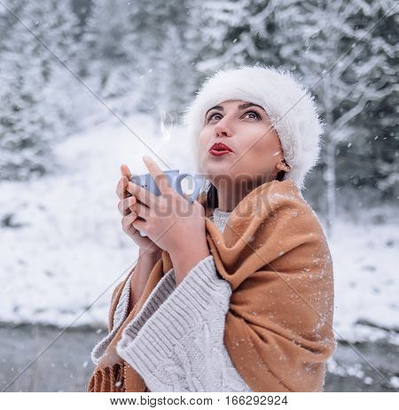 Woman with cup of hot drink in snow forest