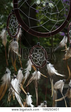 One brown dream catcher with green trees as background in the day in sunlight