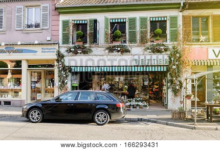 THANN FRANCE - DEC 12 2015: Luxury Audi estate car parked in front of the Vetter Florist and Jewelry store