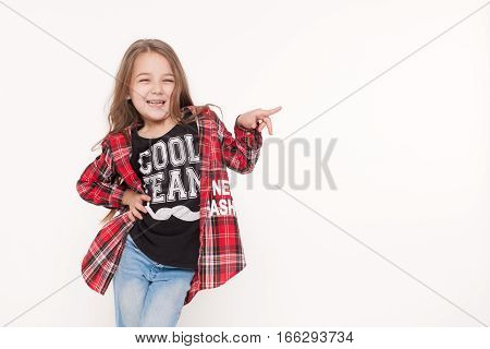 Happy Child school girl pointing with finger isolated on white.