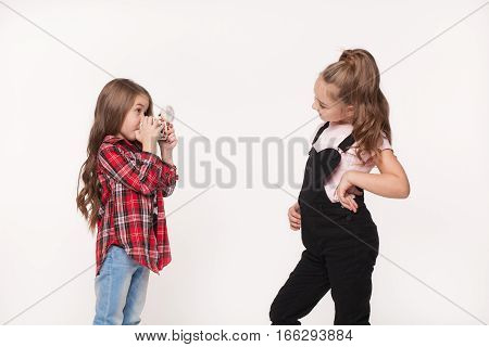 Two children girl taking a picture each other isolated white. Little kids sisters wearing stylish clothes photographing one another
