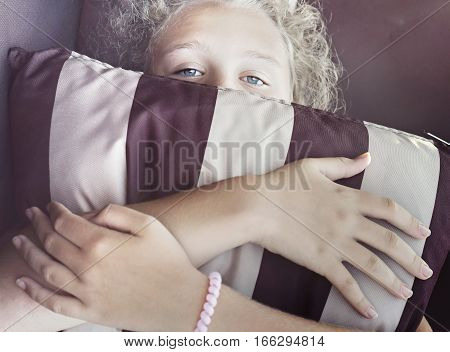 Cute thoughtful girl-teenager with blue eyes and curly blond hair is hiding her face behind a striped pillow