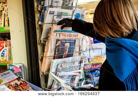 PARIS FRANCE - JAN 21 2017: Woman purchases a Financial Times Ft Weekend British newspaper from a newsstand featuring headlines with America First Donald Trump inauguration as the 45th President of the United States in Washington D.C