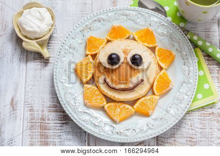 Pancakes with orange, grape and banana for kids