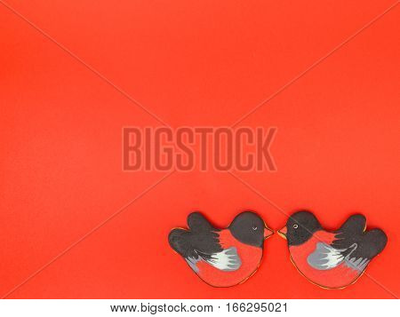 Gingerbread cookie shape of birds bullfinches Sweet cookies bullfinches on a red background