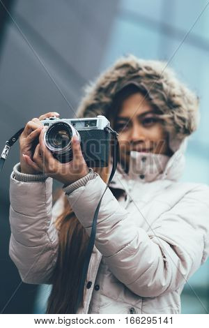 Beautiful girl photographing in cold weather, urban environment