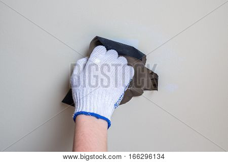 image of polishing a wall with sandpaper closeup