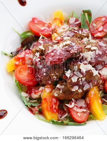 Warm salad with chicken liver in raspberry sauce on a plate