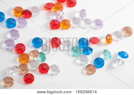 A collection of different faceted stones on a white background, the gems scattered on the table