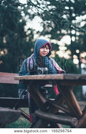 Girl siting on wooden table holding camera in her hand