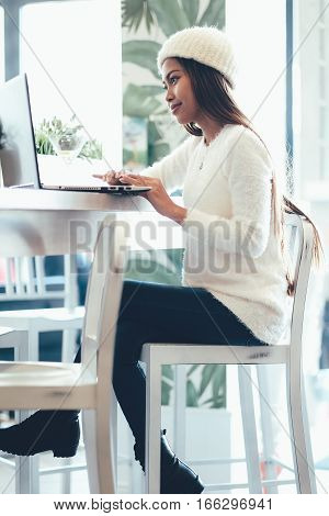 Beautiful girl networking in a cafe with laptop