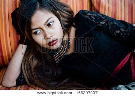 Fashionable beautiful girl posing on stripe sofa