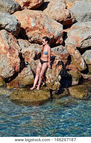 AGIOS NIKOLAOS, CRETE - SEPTEMBER 17, 2016 - Young woman leaning against the rocks enjoying the sunshine Agios Nikolaos Crete Greece Europe, September 17, 2016.