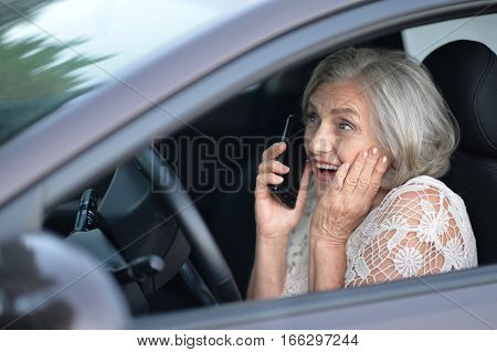 mature woman driving a car and talking on the phone