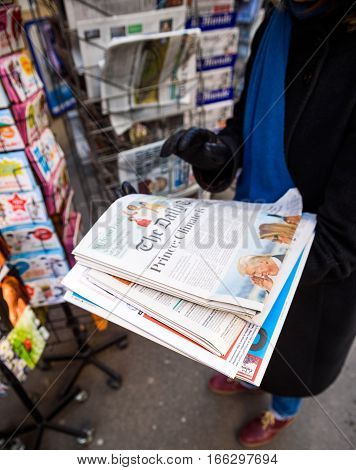 PARIS FRANCE - JAN 21 2017: Woman purchases a The Daily Telegraph British newspaper from a newsstand featuring headlines with Donald Trump inauguration as the 45th President of the United States in Washington D.C