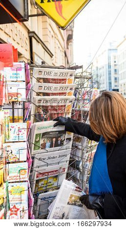PARIS FRANCE - JAN 21 2017: Woman purchases a Suddeutsche Zeitung German newspaper from a newsstand featuring headlines with Donald Trump inauguration as the 45th President of the United States in Washington D.C