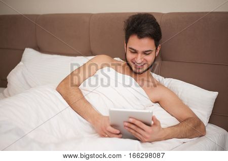 Handsome young man with stubble relaxing in bed at home and reading an ebook on his digital tablet
