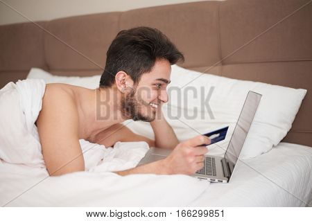 Young man holding credit card and using laptop. Online shopping concept.