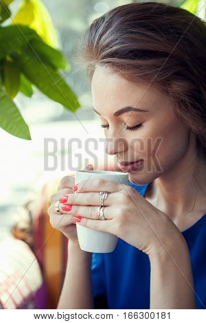 Beautiful Woman Drinking Coffe In A Cafe And Looking Down