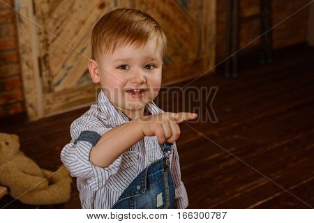 Small boy smilling in fashon jeans solo pointing on something