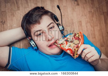 Teenager eating pizza. The concept of unhealthy lifestyle.