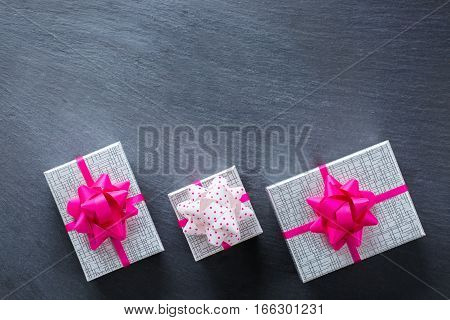 Love and still life concept. Valentines day holiday gift boxes on a grunge black table. Top view flat lay overhead, copy space background
