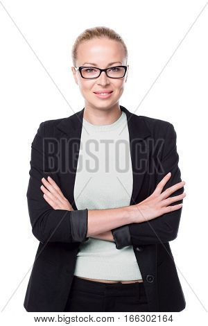Portrait of beautiful smart young businesswoman in business attire wearing black eyeglasses, standing with arms crossed against white background.
