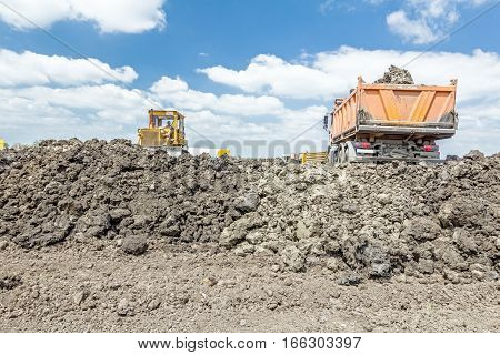 View on heavy bulldozer while he moving leveling ground at construction site. Heavy wheels are working at construction site.