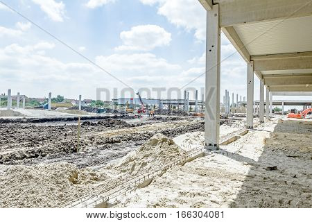 View on construction site with machinery people at work. Landscape transform into large urban area concrete hall.