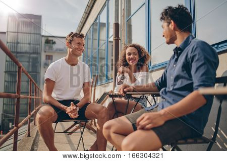 Three young friends together at outdoor cafe. Multiracial group of young people sitting around a small cafe table chatting and smiling.