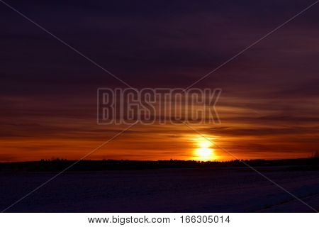 Beautiful red / orange sunset with forest silhouette.
