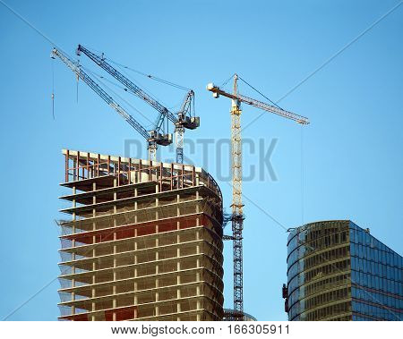 Hoisting tower cranes in construction process on top of office building construction over clear cloudless blue sky