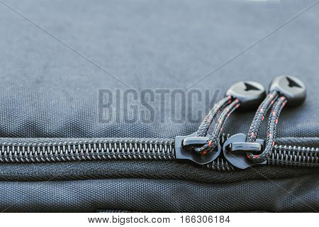 Close focus on two zippers with short striped nylon rope fastened on black surface.