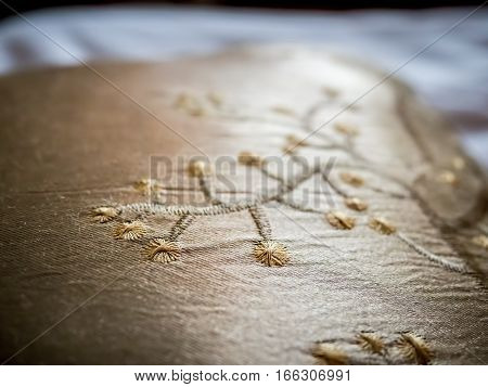 Golden color cushion cover with cherry blossom embroidery motif. High resolution, shallow depth-of-field image highlighting detailed stitching pattern.